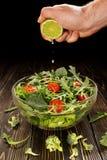 Limettensaft wird in einen Teller mit Salat zusammengedrückt Lizenzfreie Stockfotos