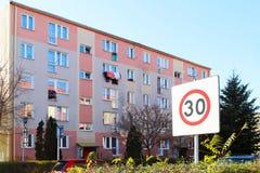 Limitazione della velocità dei veicoli in una zona residenziale a 30 Segnale stradale sui precedenti di una costruzione di appart immagini stock