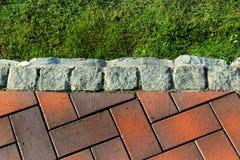 Limite o lancil entre o gramado da grama verde e o passeio telhado em um parque Fotos de Stock
