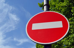 Limiting traffic sign white brick on red on sky. Limiting traffic sign white brick on red round background against blue sky and green trees Royalty Free Stock Images