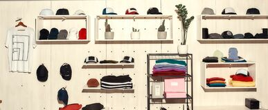 Limitless solutions. Custom apparel, clothes neatly arranged or folded on shelves. Stack of colorful clothing and