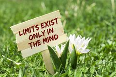 Limits exist only in the mind. On wooden sign in garden with spring flower royalty free stock image
