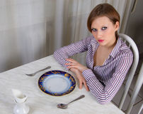 Limits to the food. A hungry girl with an empty plate. It limits herself to the food Stock Images