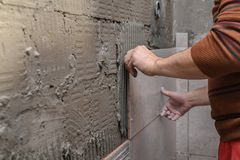 Limma tegelplattor på väggen Lägga tegelplattor på väggen arkivbild