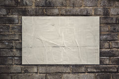 Limmat lantligt affischpapper på den gamla tegelstenväggen arkivfoton