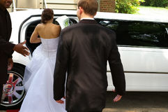 Limo ride. Bride and groom and limo Stock Image