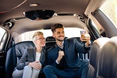 Limo selfie busines travel. Young business people taking selfie in limo Royalty Free Stock Image