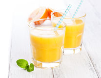Limonada amarillo-naranja del verano en vidrio con las naranjas y la paja de sangre en una tabla de madera Fotos de archivo