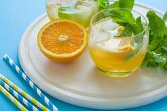 Limonada anaranjada con las rebanadas de naranja, de hielo y de menta en fondo azul Fotografía de archivo libre de regalías