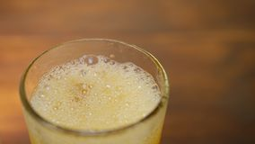 Limonada anaranjada que vierte en vidrio fr?o con el cubo de hielo almacen de video