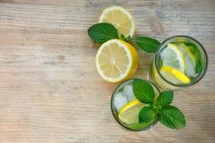 Limonada caseiro com gelo nos vidros em um fundo de madeira Água com limão, hortelã e gelo Conceito da saúde Copie o espaço Imagens de Stock