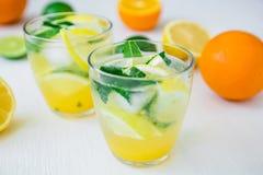 Limonada de la fruta cítrica con la cal, las hojas de menta y el limón en vidrios en la tabla blanca Imagenes de archivo