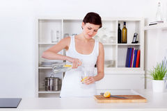 Limonada de preparação e bebendo da jovem mulher em sua cozinha fotos de stock royalty free
