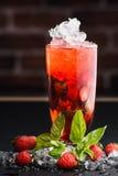 Limonada del cóctel de la fresa en un fondo uniforme oscuro con la fresa Imagenes de archivo