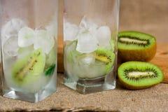 Limonada do quivi, água com gelo, partes de fruto em um copo de vidro Café da manhã da desintoxicação do verão em um fundo de mad Imagens de Stock