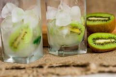 Limonada do quivi, água com gelo, partes de fruto em um copo de vidro Café da manhã da desintoxicação do verão em um fundo de mad Imagem de Stock Royalty Free