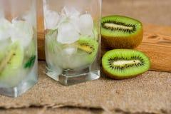 Limonada do quivi, água com gelo, partes de fruto em um copo de vidro Café da manhã da desintoxicação do verão em um fundo de mad Foto de Stock