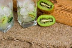 Limonada do quivi, água com gelo, partes de fruto em um copo de vidro Café da manhã da desintoxicação do verão em um fundo de mad Imagem de Stock