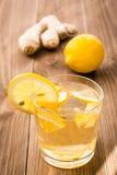 Limonada en un vidrio, un limón y un jengibre en una tabla de madera Fotos de archivo
