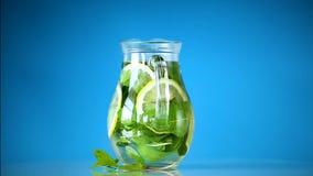 Limonada fr?a fresca con los limones y la menta en una garrafa aislada en azul metrajes