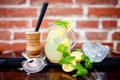 Limonada fresca, helada de la menta en un jarro con el limón cortado, menta Foto de archivo