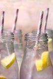 Limonada rosada en botellas con la paja rosada y blanca Imagen de archivo libre de regalías
