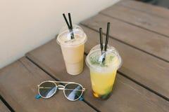 Limonada sabrosa con los fruts, el latte del hielo y las gafas de sol en la tabla fotos de archivo