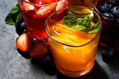 Limonadas de la fruta fresca en el surtido en la tabla oscura, visión superior Imagenes de archivo