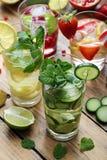 Limonadas frescas con las fresas, los limones, el granate, los pepinos y las hojas de menta Fotografía de archivo libre de regalías