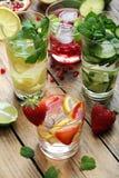Limonadas frescas con las fresas, los limones, el granate, los pepinos y las hojas de menta Fotos de archivo libres de regalías