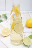 Limonade dans des deux pots avec des tranches de chaux et de citron Image libre de droits