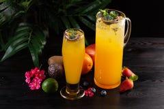 Limonade de mangue - passiflore comestible de passiflore dans une cruche et un verre et un fruit sur un fond en bois image stock