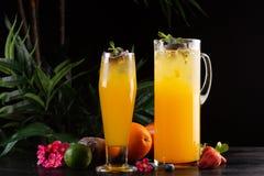 Limonade de mangue - passiflore comestible de passiflore dans une cruche et un verre et un fruit sur un fond en bois image libre de droits