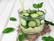 Limonade faite maison de concombre et de menthe dans un verre sur un fond en bois blanc photos stock
