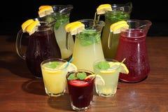 Limonade im Krug und in den Zitronen mit der Minze auf dem Tisch Innen Rosa Limonade mit Zitrone, Kalk und Erdbeeren Lizenzfreie Stockfotos