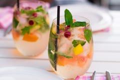 Limonade med bär i glasföremål på trätabellen på ljus suddighet Arkivfoto