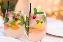 Limonade med bär i glasföremål på trätabellen på ljus suddighet Royaltyfri Fotografi