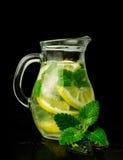 Limonade met ijs en munt in een glaswaterkruik Stock Afbeeldingen