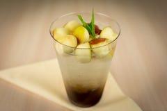 Limonade mit Apfelstücken auf Holztisch Lizenzfreie Stockfotos