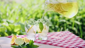 Limonade mit Eis-, Orangen- und Kalkscheiben in einem Glas stock video