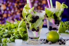 Limonade mojito mit Kalk, schwarzer Johannisbeere und Minze Stockfotografie