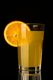 Limonade orange avec le morceau d'orange dans le verre sur le fond noir Photographie stock libre de droits