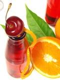 Limonade rouge dans des bouteilles avec la cerise sur le fond blanc image libre de droits