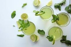 Limonata casalinga fresca con il limone, la limetta e la menta in vetro su fondo bianco ed ingredienti che mettono sulla tavola Immagine Stock Libera da Diritti