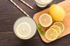 Limonata con il limone fresco della fetta su fondo di legno fotografia stock libera da diritti
