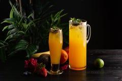 Limonata del mango - frutto della passione in una brocca e un vetro e una frutta su un fondo di legno immagini stock