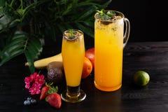 Limonata del mango - frutto della passione in una brocca e un vetro e una frutta su un fondo di legno immagine stock libera da diritti