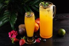 Limonata del mango - frutto della passione in una brocca e un vetro e una frutta su un fondo di legno fotografie stock libere da diritti