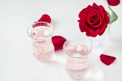 Limonata di rinfresco dell'acqua di rose di due tazze con i cubetti di ghiaccio ed il fiore di Rosa in vetro e petali su fondo bi Immagini Stock Libere da Diritti