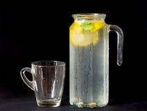 Limonata fresca in brocca con vetro, la menta ed il limone isolati sul bla immagini stock